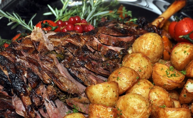 Leg of lamb roasted with rosemary, summer potatoes and tomato