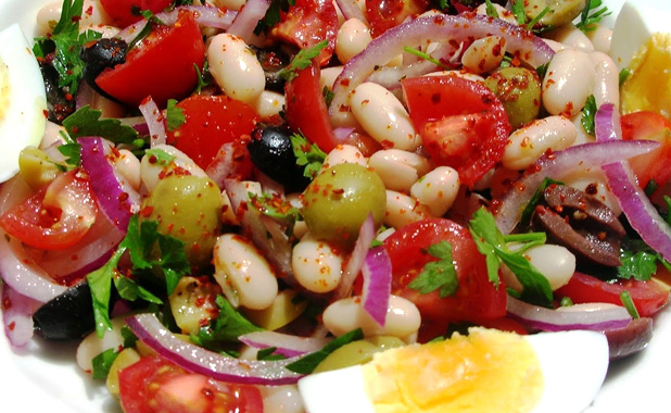 Bean salad with olives, fresh parsley and onions